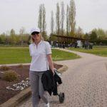 Lächelnede Golferin auf dem Weg zum Abschlag