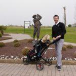 Golfer mit Golfbag vor einer Golferstatue