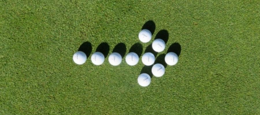 weiße Golfbälle zum einem Pfeil gelegt