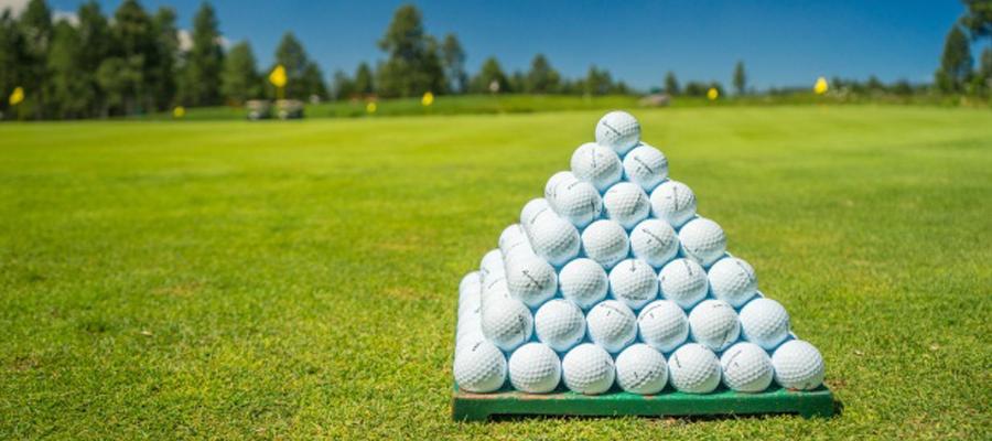 Golfbälle zur Pyramdie gestapelt auf Golfplatz